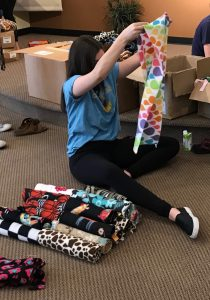 Folding up fleece scarves on packing day, 2017